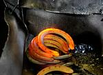 Glowing red-hot steel horseshoes heated in a 2200 degree gas-fired furnace and bent to shape by a powerful machine, sit in a bin.